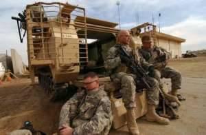 Солдаты американской армии отдыхают за своим M113 в Ираке. Заметьте, как решетчатая броня увеличила ширину машины